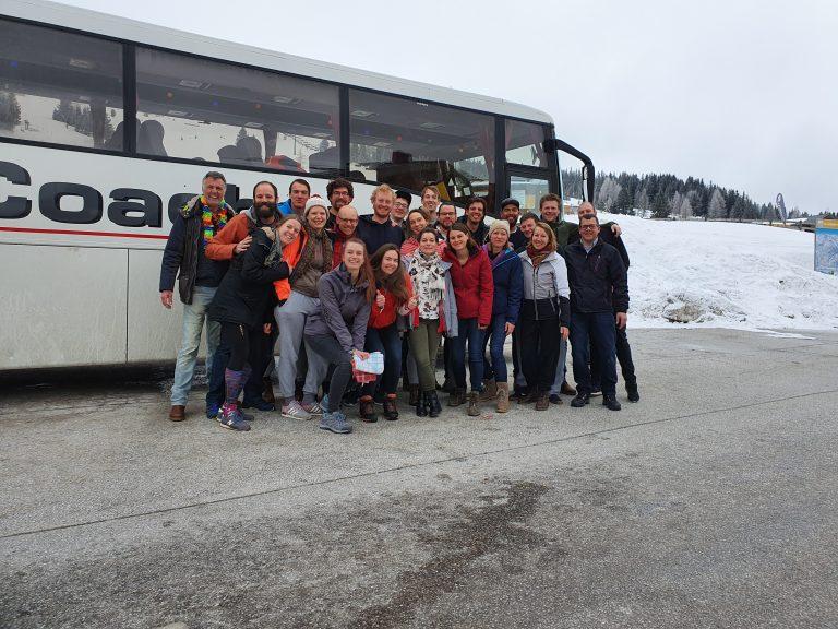 Groep skiërs en snowboarders voor bus.