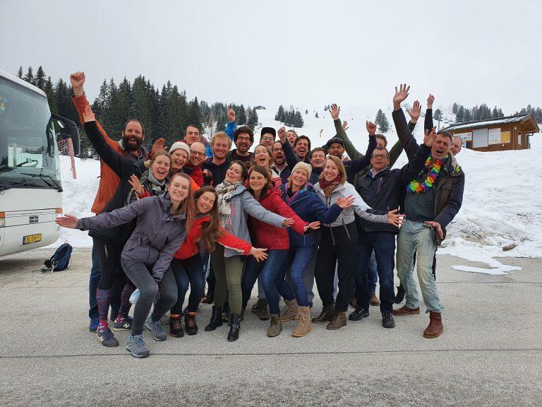 Groep skiers en snowboarders juichen voor piste en bus.